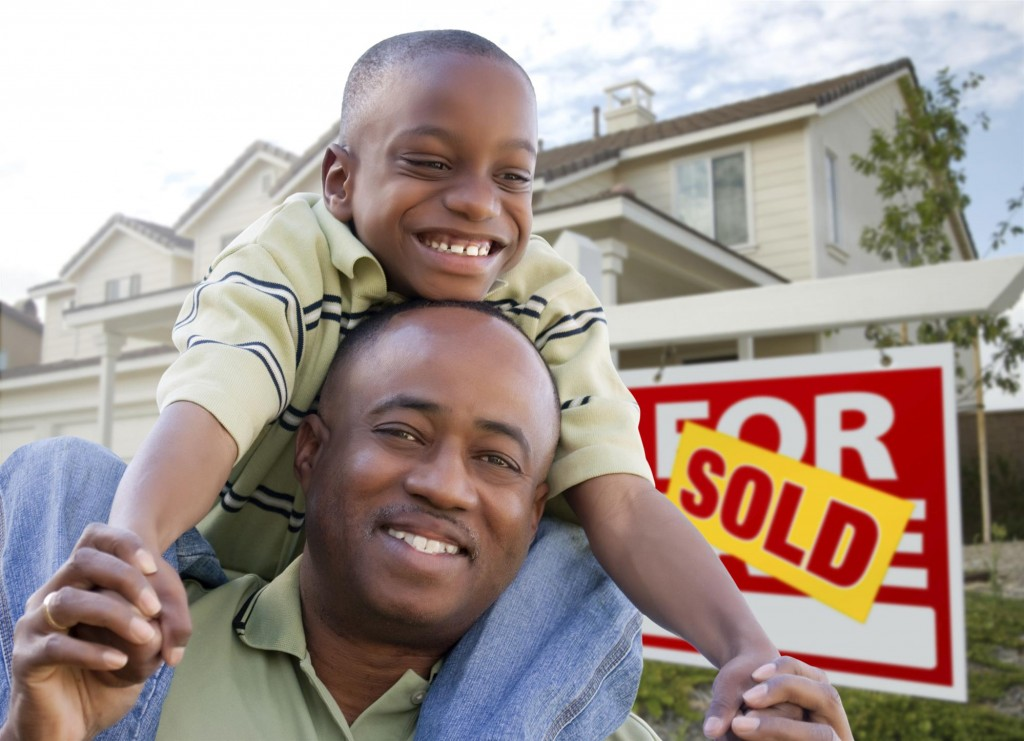 Father and Son outside sold home